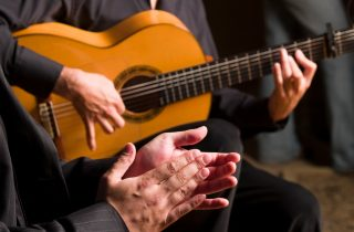 Close-up of flamenco guitar and hands clapping